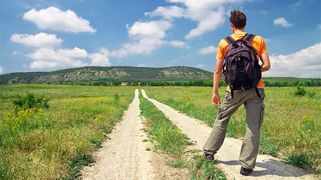 Ein Wanderer wandert quer über ein Feld.