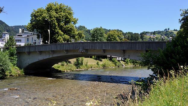 Eine Holzbrücke über einem Fluss.