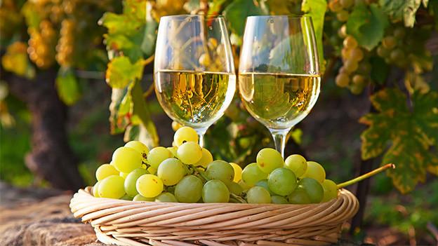 Zwei Gläser Wein und weisse Trauben.