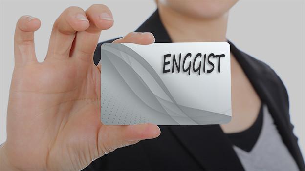 Konturen einer Frau, die eine Visitenkarte mit dem Namen Enggist zeigt.