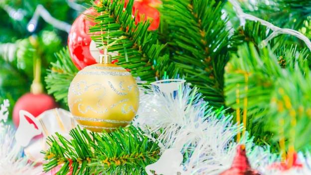 Eine Christbaumkugel hängt am Weihnachtsbaum.