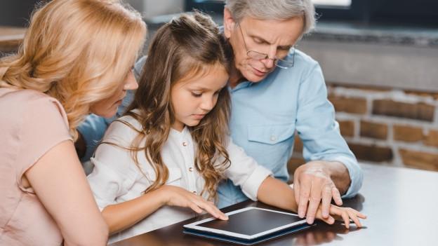 Kind erklärt seinen Grosseltern den Umgang mit einem Tablet.