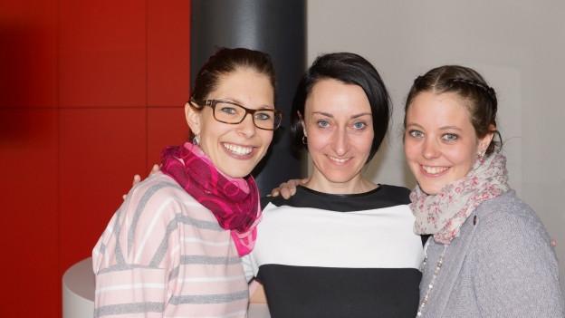 Drei Damen posieren für Foto.