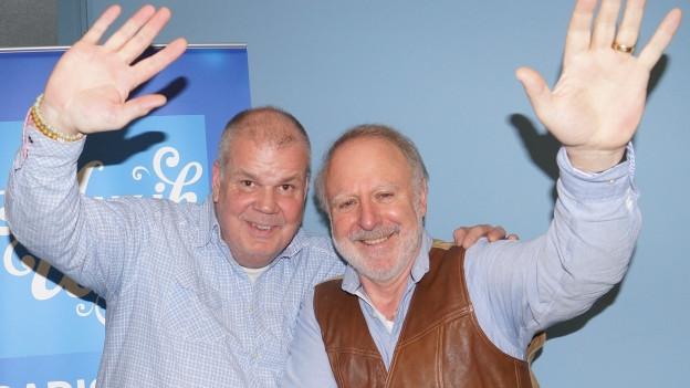 Zwei Männer stehen vor SRF Musikwelle Logo.
