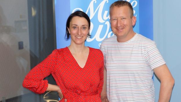 Reto Kamer zu Besuch bei Renate Anderegg. Die beiden posieren vor dem SRF Musikwelle-Logo.