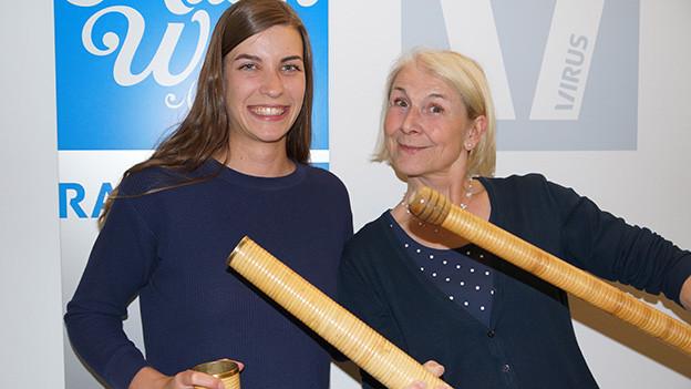 Zwei lachende Frauen mit Teilen eines Alphorns.