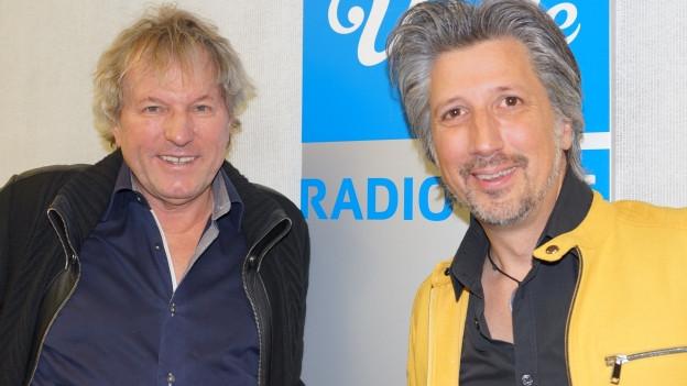 Zwei Männer vor Musikwelle-Logo.