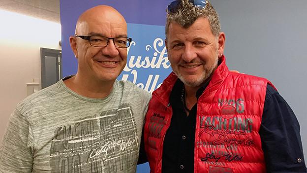 Zwei Männer vor einem blau-weissen Logo.