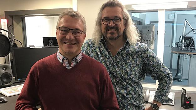 Zwei Männer vor Mikrofonen in einem Radiostudio.