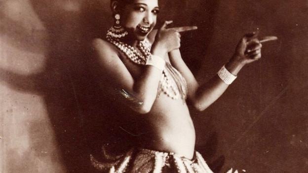 Schwarze Frau im Bananenröckchen. Historische Aufnahme.