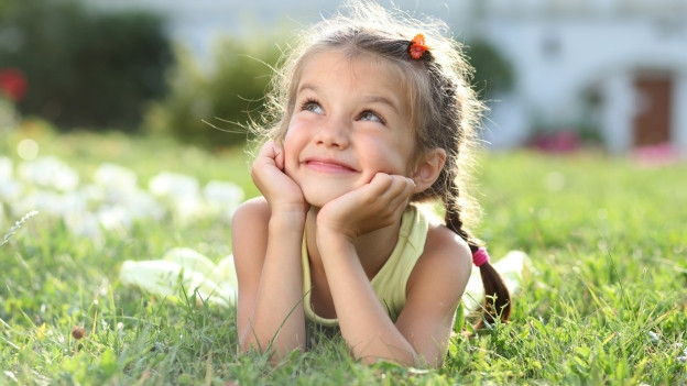 Kleines Mädchen glücklich auf Frühlingswiese.