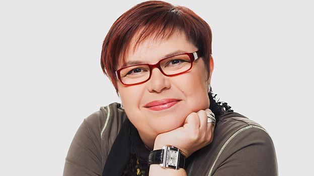 Porträtbild von einer Frau mit kurzen Haaren und Brille.