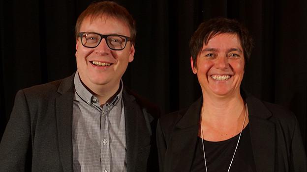 Ein Moderator und eine Moderatorin vor einem dunklen Vorhang.