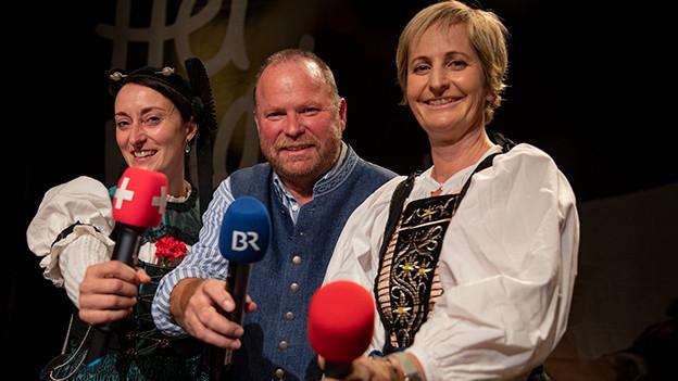 Zwei Frauen und ein Mann mit Mikrofonen.