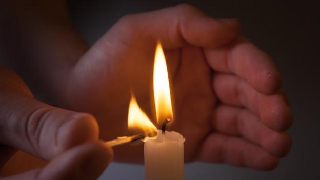 Jemand zündet eine Kerze an.