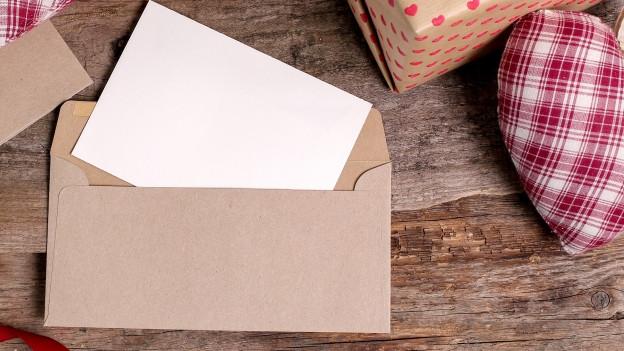 Ein Brief liegt neben vielen Päckli auf dem Tisch.