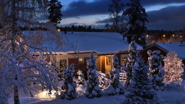 Ein beleuchtetes Einfamilienhaus in der Nacht im Winter.