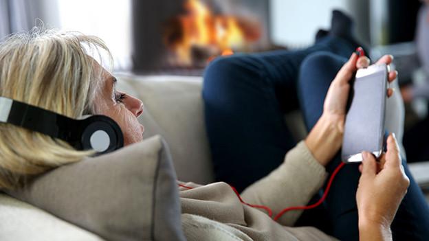 Eine Frau auf einem Sofa mit Kopfhörern und Smartphone.