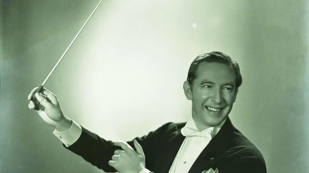 Mann mit Dirigentenstab in der Hand.