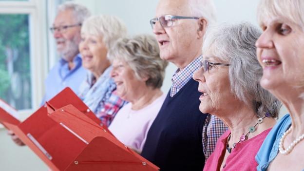 Senioren singen in einem Chor.