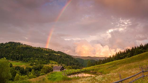 Ein Regenbogen über einer Alp.