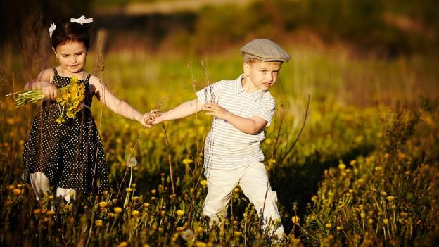 Zwei Kinder gehen Hand in Hand über Frühlingswiese und sammeln Blumen.