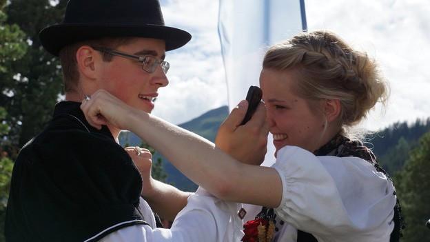 Ein junges Paar in Tracht tanzt.