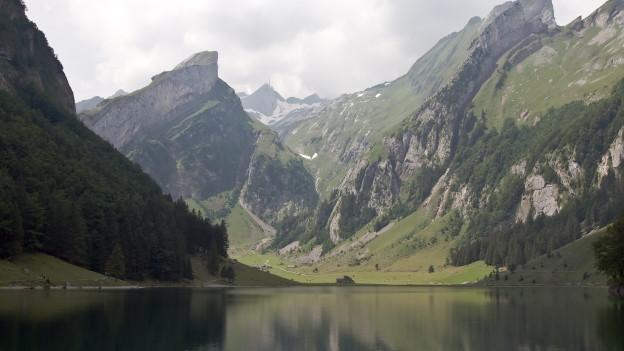 Berge mit etwas Schnee, im Vordergrund ein See.