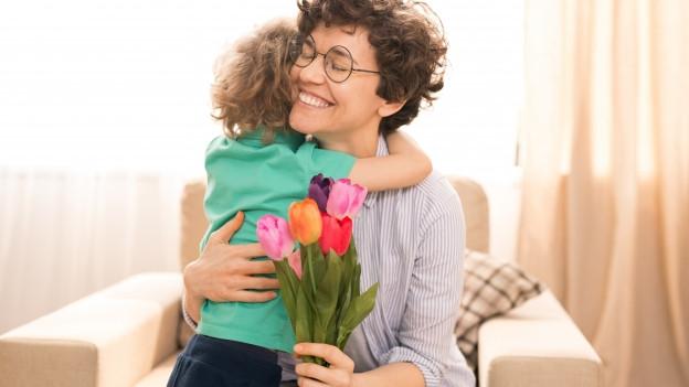 Kind überreicht Mama Blumen.