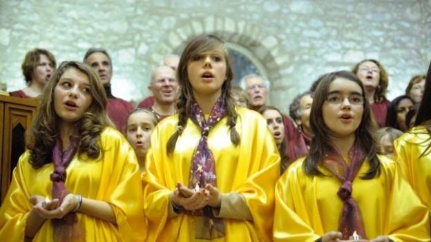 Mädchenchor in gelben Roben.