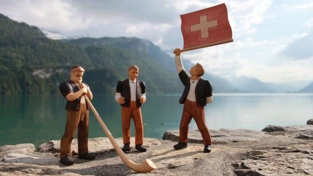 Holzfiguren die Alphorn spielen und Fahnen schwingen.