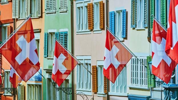 Schweizer Fahnen an einer farbigen Häuserwand.