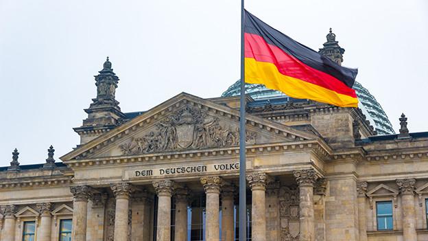 Eine Flagge weht vor einem Regierungsgebäude.