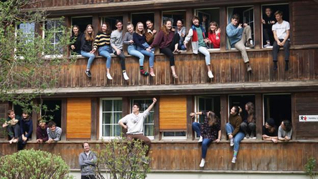 Junge Sängerinnen und Sänger schauen aus zahlreichen Fenstern eines Bauernhauses hinaus.