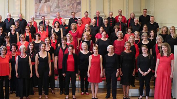 Chor in rot-schwarzer Kleidung.