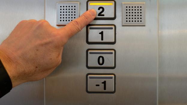 Jemand drückt auf den Knopf im Fahrstuhl.