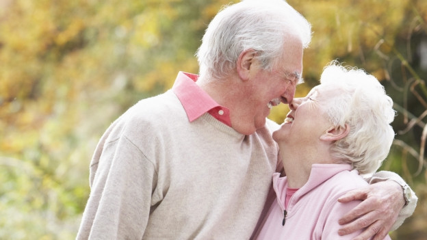 Zwei Senioren küssen sich.