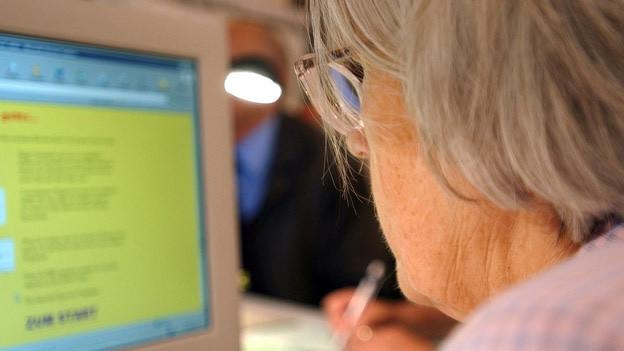 Eine ältere Frau am Computer.
