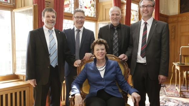 Frau auf Stuhl umrahmt von Herren im Anzug.