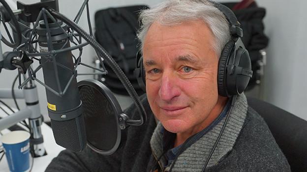 Ein Mann vor einem Mikrofon.