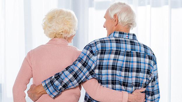 Ein altes Ehepaar steht Arm in Arm vor einem Fenster.