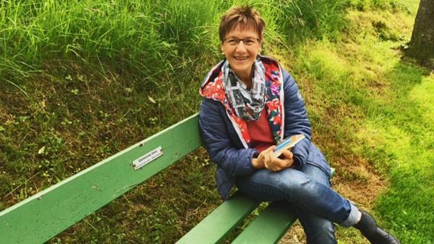 Anita Glunk sitzt auf einer grünen Bank.