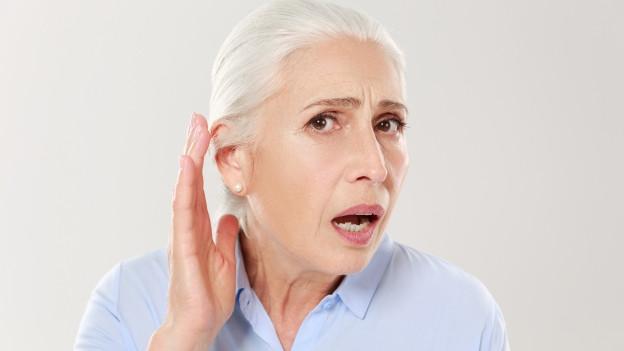 Eine Frau hält sich ihre Hand an ihr Ohr.