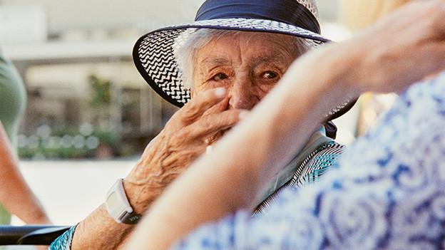 Eine alte Frau mit Hut.