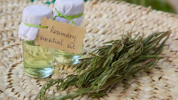 Rosmarinöl in einem Fläschchen daneben frischer Rosmarin