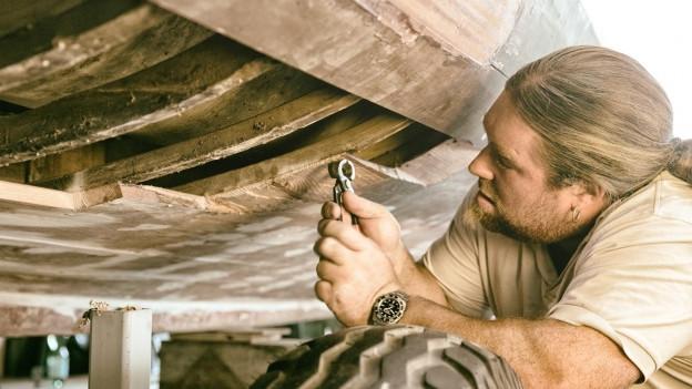 Stefan Züst hält eine Zange in der Hand und arbeitet an einem Holzboot.