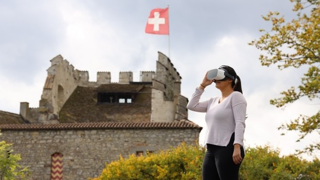 Eine Frau schaut in eine VR-Brille und steht vor dem Schloss Habsburg.