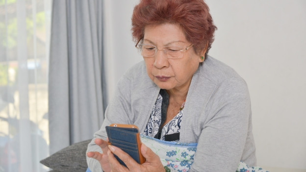 Eine Seniorin schaut in ihr Smartphone.