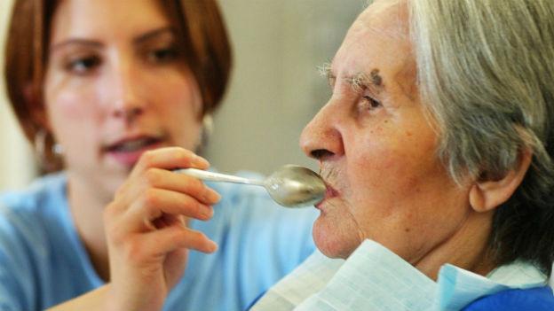 Frau hilft älterer Patientin beim Essen.