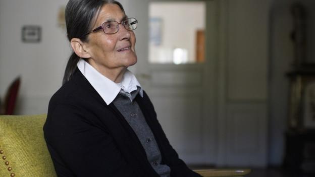 Seniorin in schwarzer Kleidung sitzt auf Stuhl.